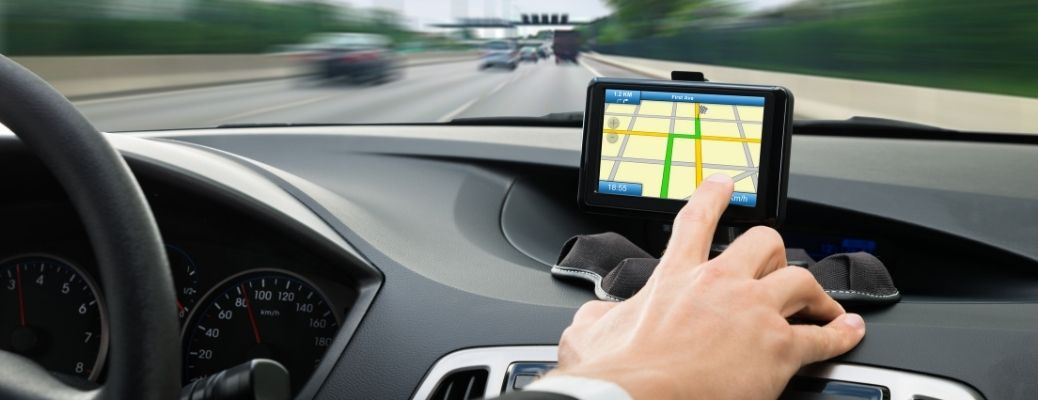 person's hand using the GPS system of a car