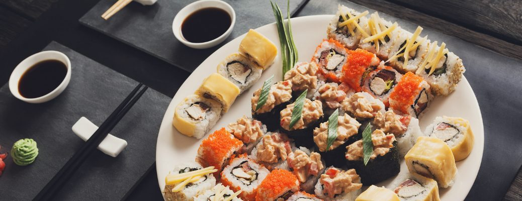 Large Plate of Sushi with Chopsticks and Soy Sauce