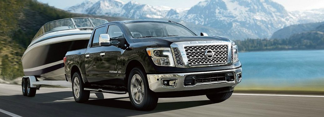 2018 Nissan Titan black side view with a boat