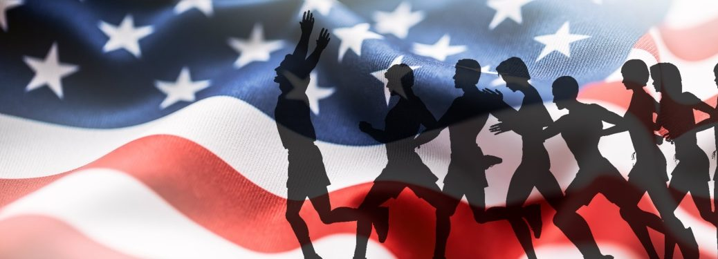 Silhouette of runners in front of an American flag