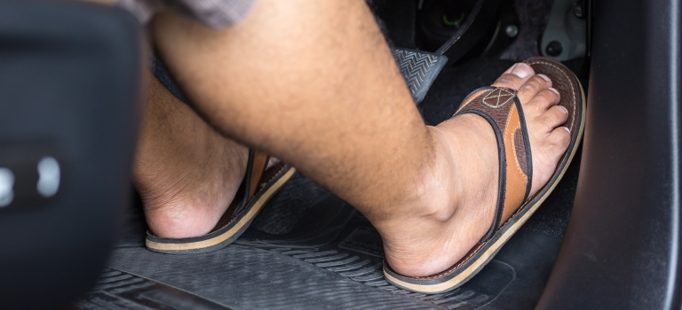 Man's feet on the pedals of a car with flip-flops