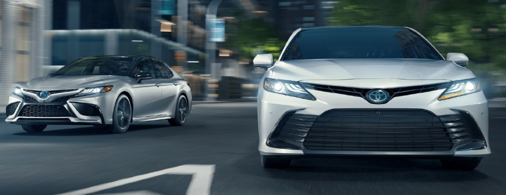 Two 2021 Toyota Camry vehicles on a roadway where it splits and each begins to go in a different direction
