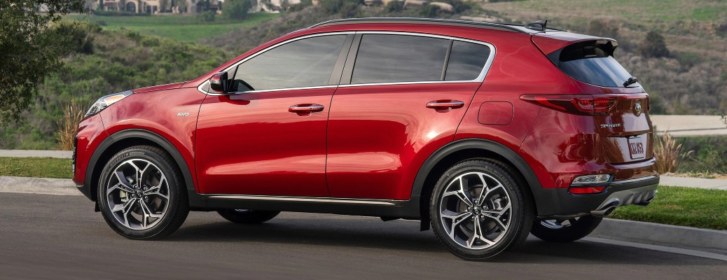 2020 Kia Sportage red profile view driving past green valley