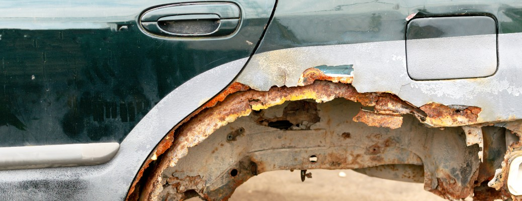 rusted out wheel well of green car with door handle