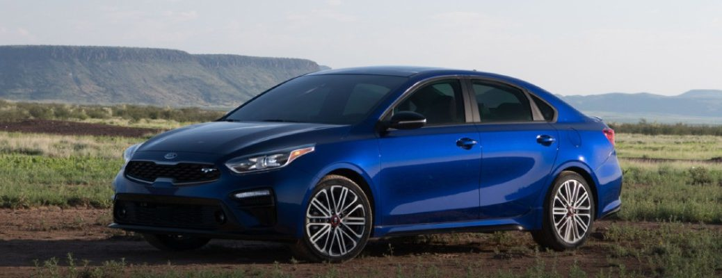 2020 Kia Forte blue exterior shot showing driver side and front parked on dirt in field