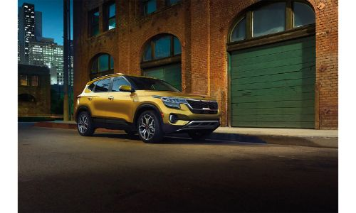 2021 Kia Seltos yellow paint parked outside brick building at night