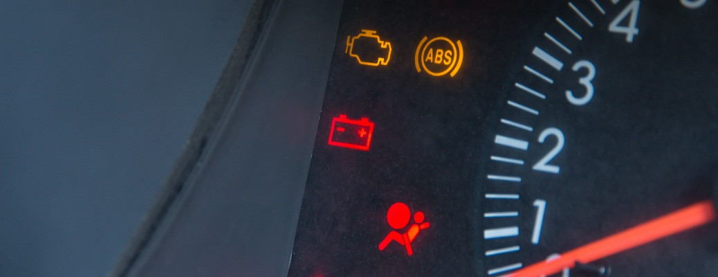 close up of warning lights on dashboard near rpm gauge