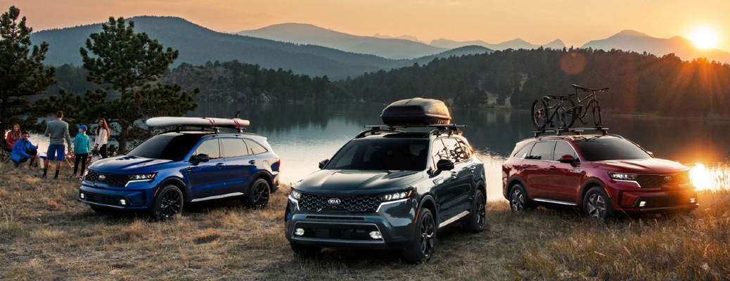three 2021 Kia Sorento models parked on hill near lake with mountains