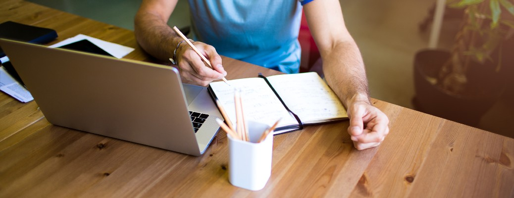person writing on pad of paper while referencing online materials cup of pencils wood table