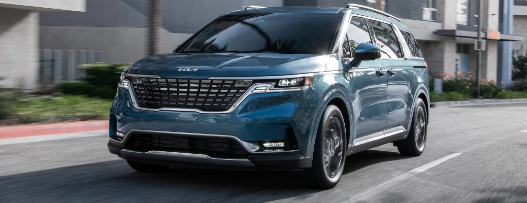 2022 Kia Carnival blue driving past townhomes