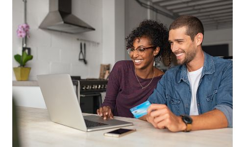couple shopping online with laptop holding credit card