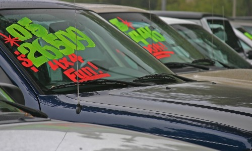 used cars with prices written in washable paint