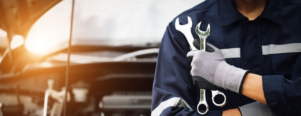 Mechanic holding spanners in a service center