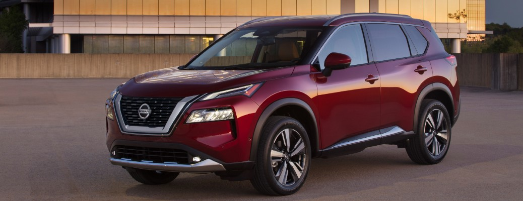 2021 Nissan Rogue exterior shot with red paint color parked in front of a glass window building reflecting a sunset