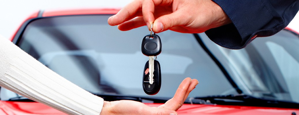 a car delivery salesman handing over the car keys to a new vehicle owner