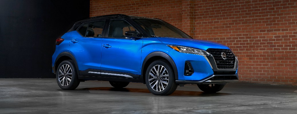2021 Nissan Kicks exterior promo shot with blue paint color parked in a hangar next to a brick wall