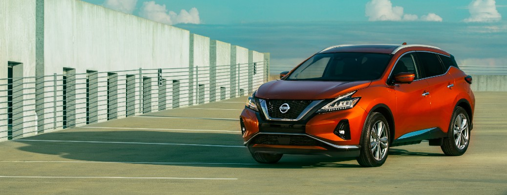 2021 Nissan Murano exterior shot with orange red paint colour parked on a beach parking lot near the sea