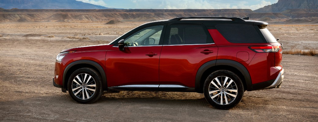 2022 Nissan Pathfinder exterior side shot with red paint color parked on a dusty desert plain