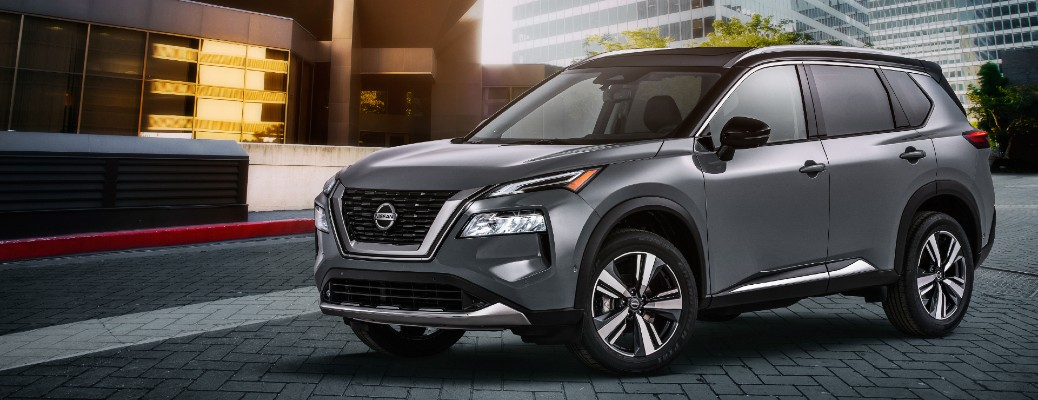 2021 Nissan Rogue exterior shot with grey metallic paint color parked on a stone tile road outside of a hotel entrance