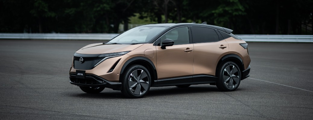 Nissan Ariya all-electric crossover model exterior shot premiere debut promo shot parked on an empty lot with a brown tan beige color