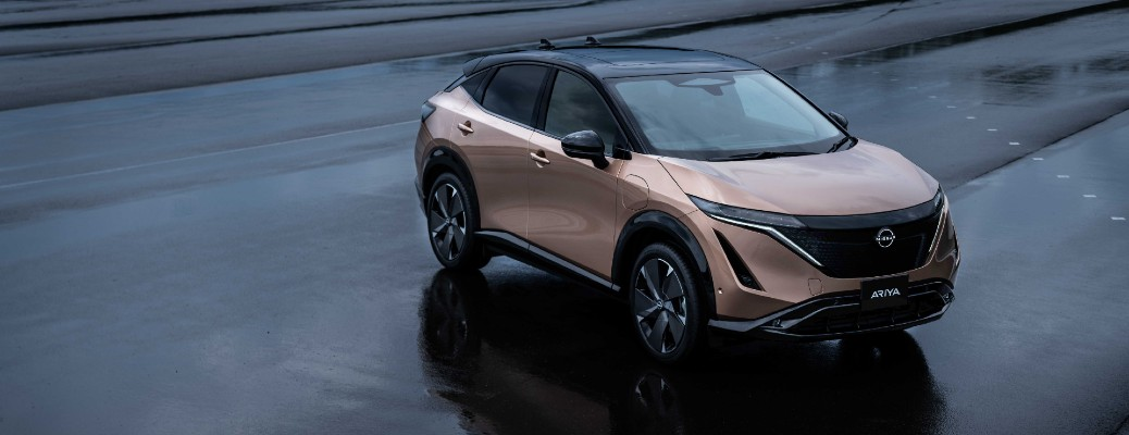 Nissan Ariya all-electric crossover model exterior overhead shot premiere debut promo shot parked on an empty wet lot with a brown tan beige color