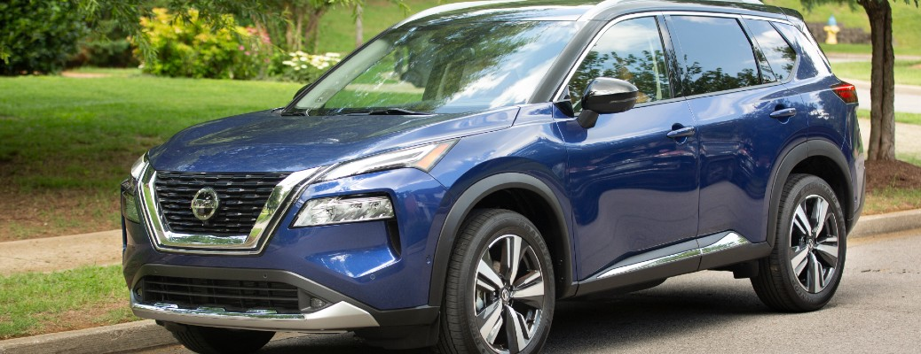 2021 Nissan Rogue exterior shot with dark blue paint color parked on the side of a street near a park field of grass
