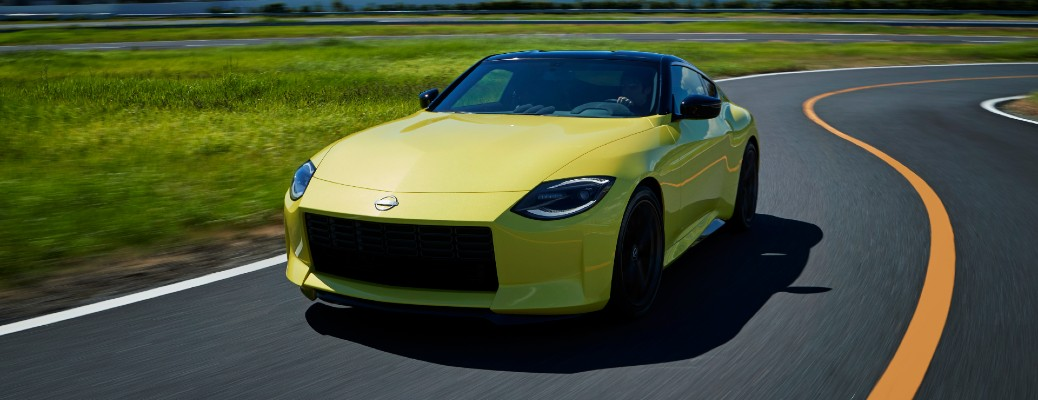 Nissan Z Proto exterior promo shot with yellow paint color driving on a country highway road