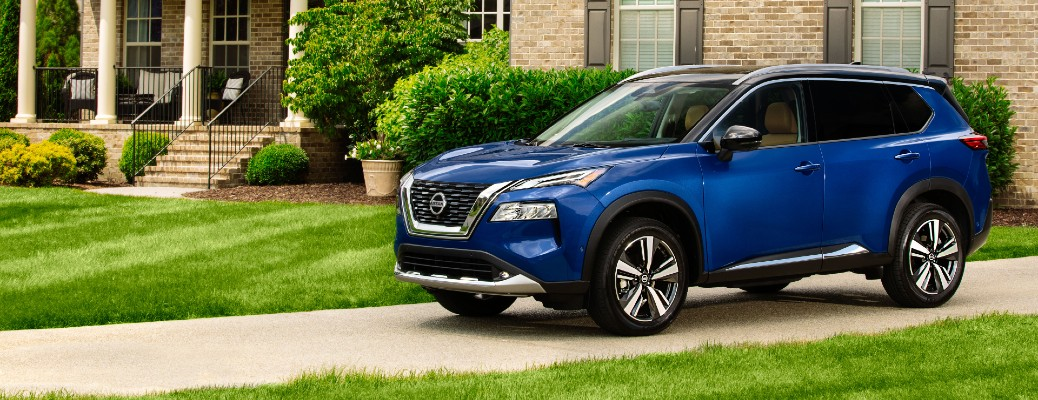2021 Nissan Rogue exterior shot with Caspian Blue paint color parked on the driveway of a fancy brick house with a green grass lawn