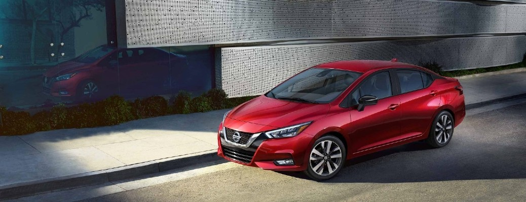 2021 Nissan Versa exterior shot with red paint color parked on the side of street with its image reflected in glass