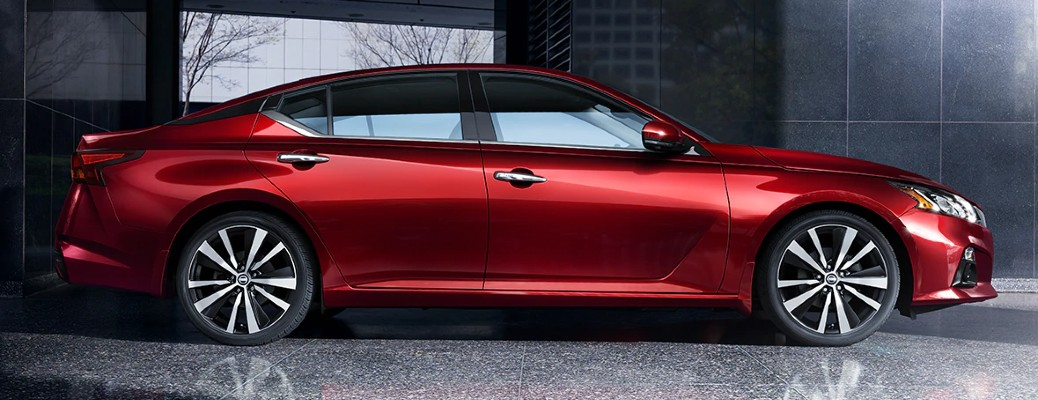 2021 Nissan Altima exterior side shot in Scarlet Ember Tintcoat parked on a marble floor