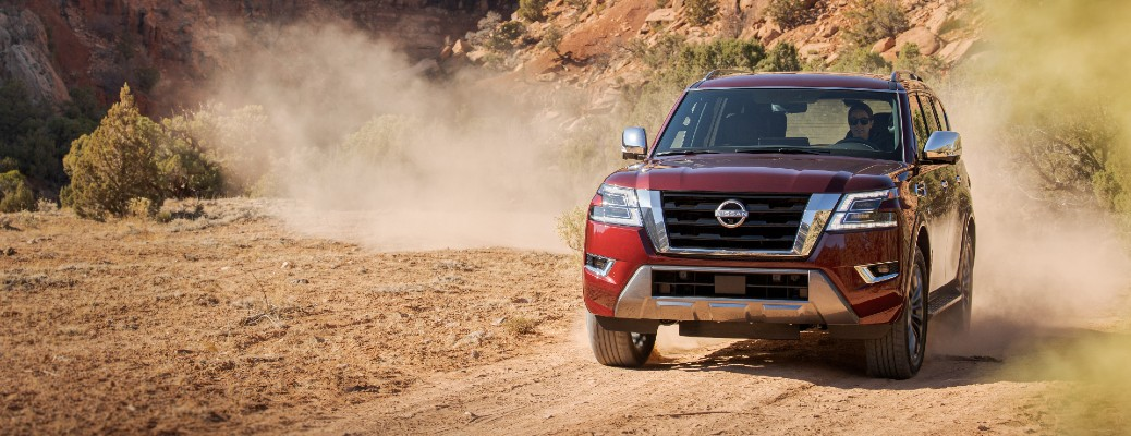 2021 Nissan Armada exterior shot with dark red paint color driving on a desert road near cliffs and a dust cloud
