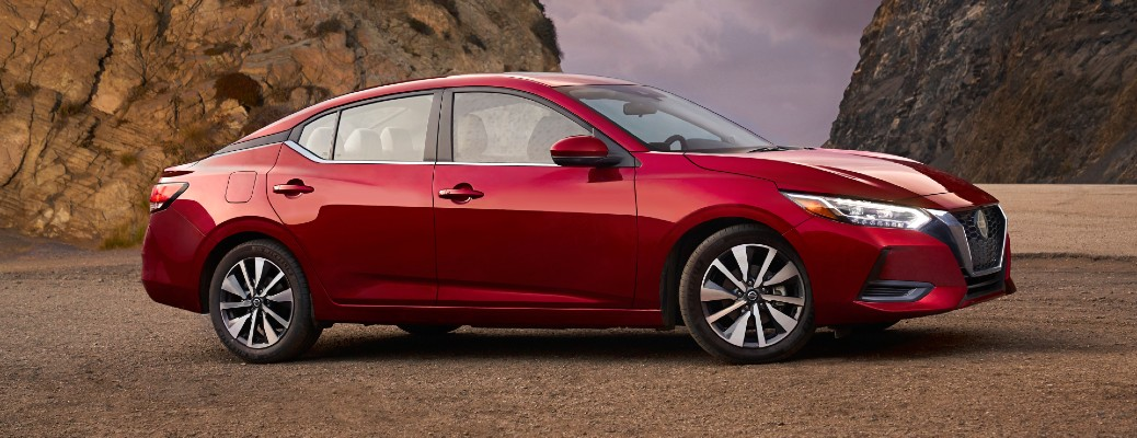 2021 Nissan Sentra exterior side shot with Scarlett Ember Tintcoat colour option parked near rocky cliffs