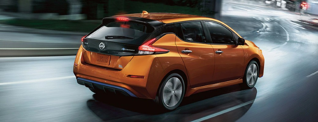 2021 Nissan LEAF exterior rear shot with Sunset Drift colour option driving on a wet and winding road