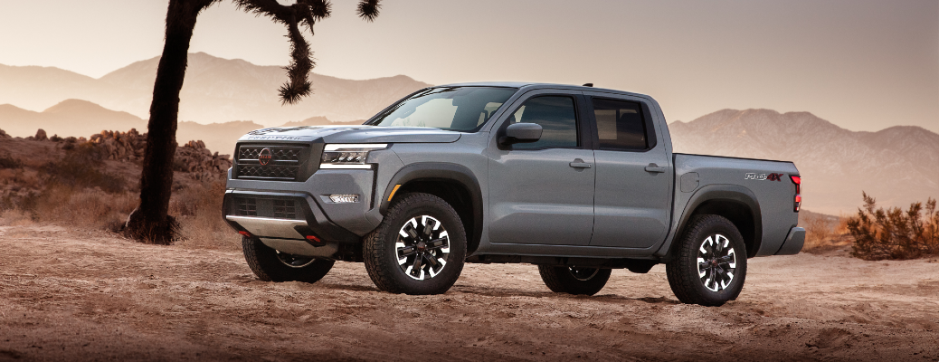 2022 Nissan Frontier exterior side shot with gray paint color parked in a desert landscape