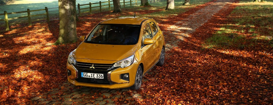 2021 Mitsubishi Mirage exterior overhead shot with gold paint color parked on a brick park trail surrounded by fall leaves