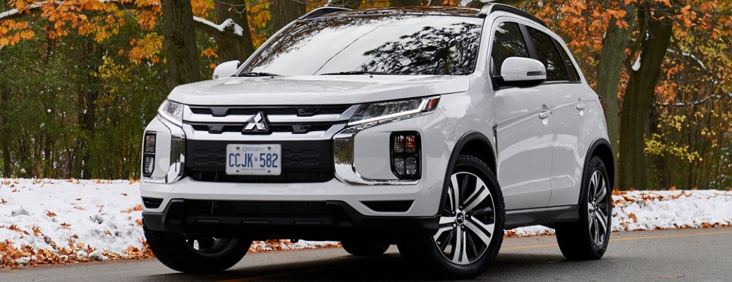 2020 Mitsubishi RVR with Pearl White paint color parked under an autumn tree next to a snowy field