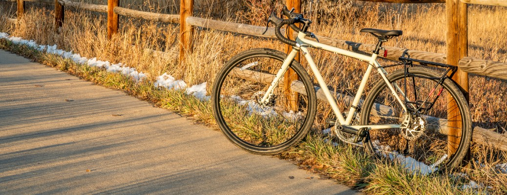 a touring bike with a white frame parked on a bike trail and leaning against a wooden fence