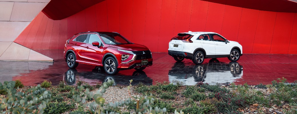 2022 Mitsubishi Eclipse Cross restyled models in red and white parked next to a red sculpture near a field of plants and rocks