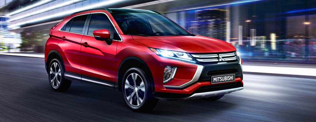 2020 Mitsubishi Eclipse Cross exterior shot with Red Diamond paint colour option driving through a city at night