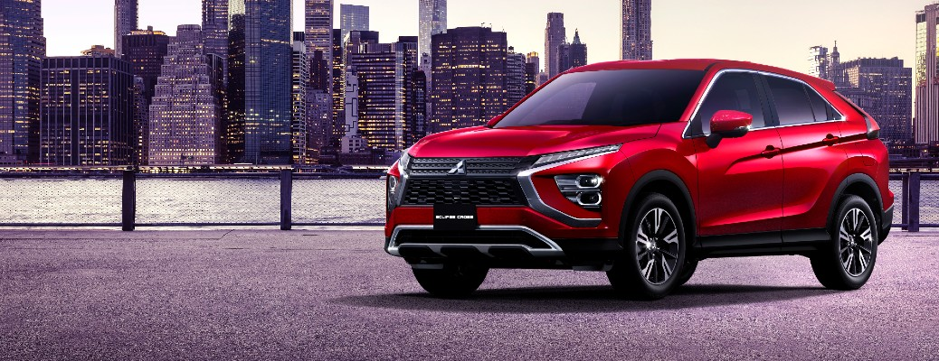 2022 Mitsubishi Eclipse Cross redesign exterior shot with red paint colour parked on a dock with a city skyline background