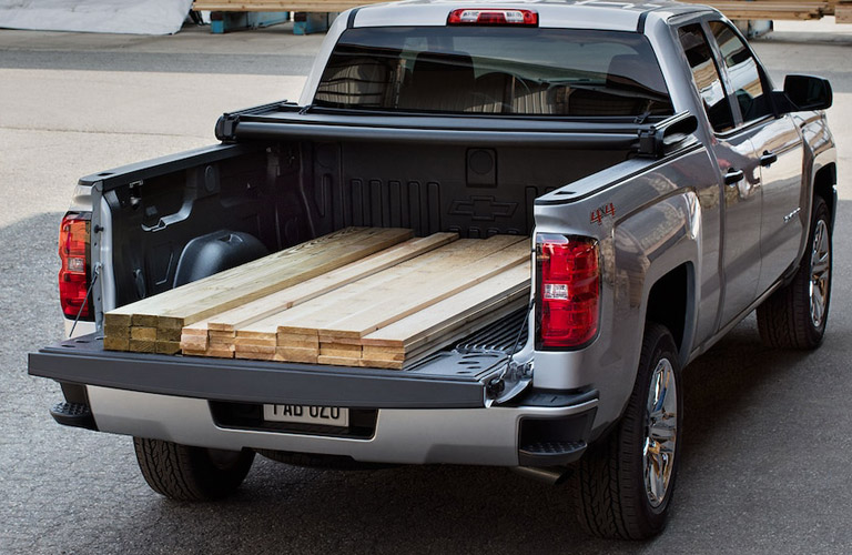 back of Chevy Silverado with payload full of boards