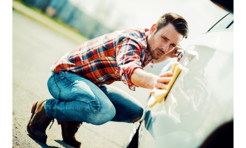 Man wiping down his car by hand