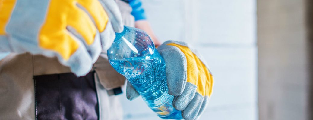 Work gloves unscrewing a bottle of water