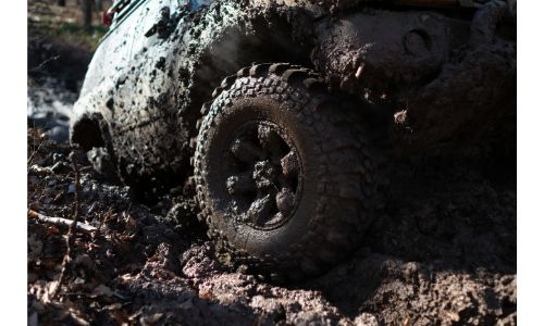 Mud covered vehicle driving off-road
