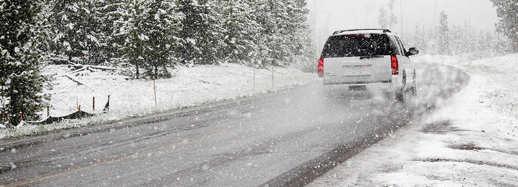 A white SUV driving on a snowy road