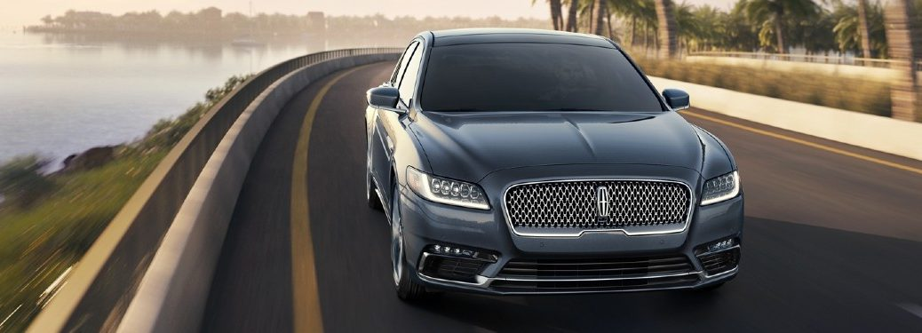 2020 Lincoln Continental exterior front shot with light blue paint color driving down a tropical highway near the sea