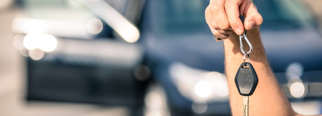 man holding up car keys in front of car with open passenger door