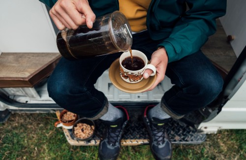 person pouring coffee from french press into mug outside