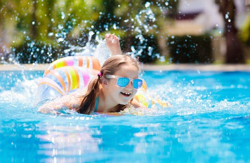 young girl swimming in pool with floaty