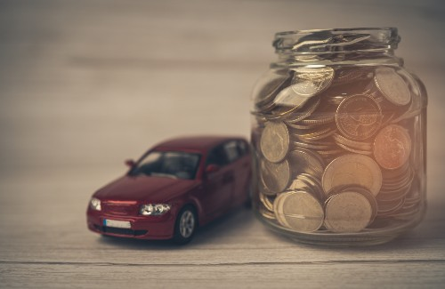 toy red car next to jar of coins on wood table